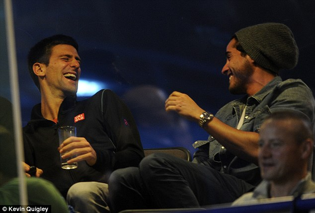 All smiles: Tennis star Novak Djokovic laughs with a friend at Stamford Bridge