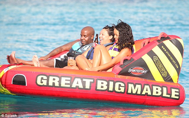 Great big Mable: Rihanna and her pals lie back on an inflatable with a few beer