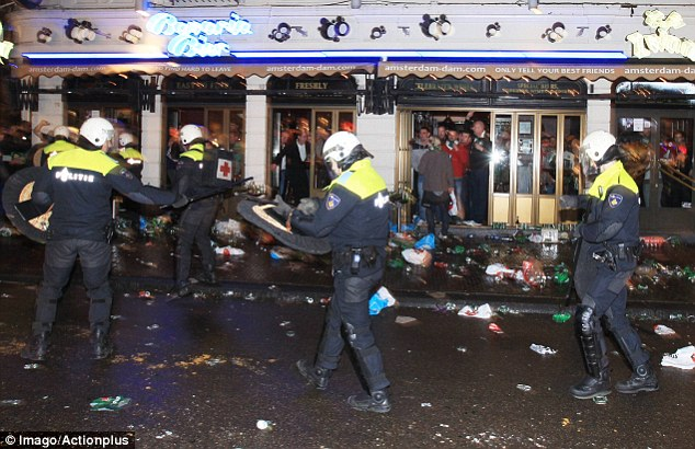 Sweeping through: Fans watch from a packed bar as the police pass by