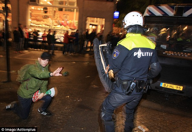 Hold off: One fan gestures towards an incoming police officer from his knees