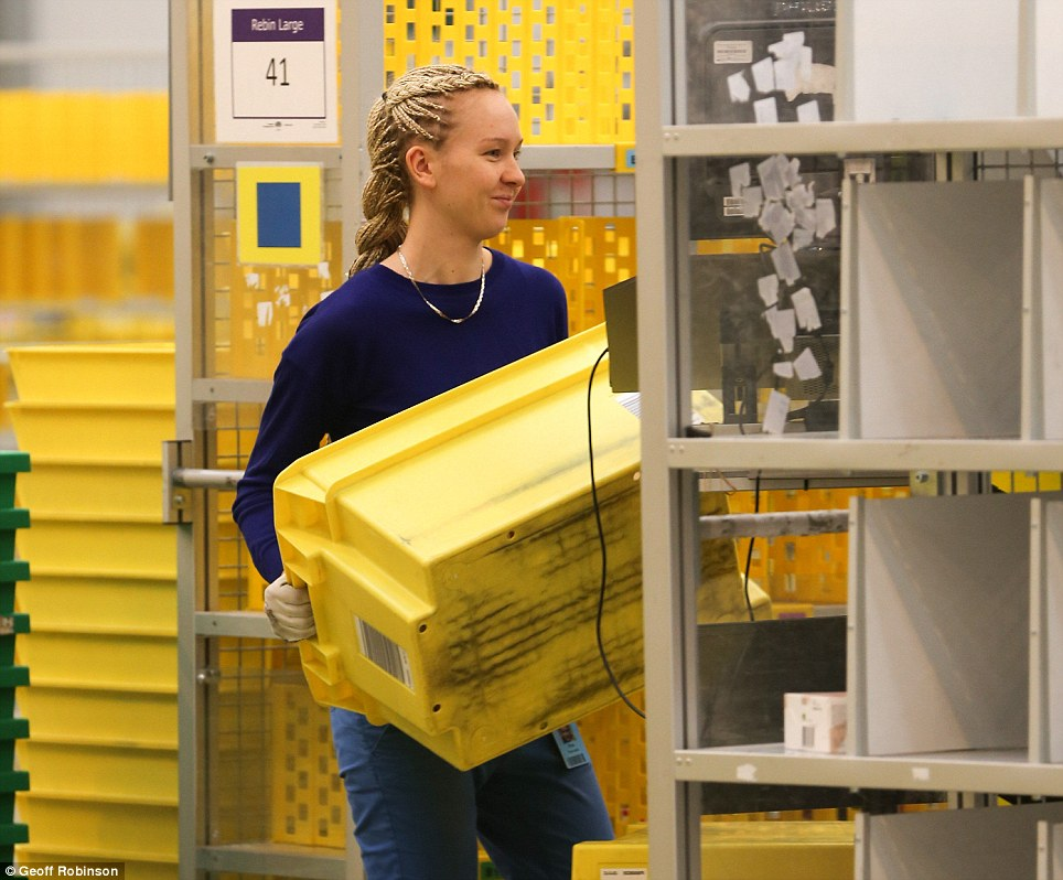 Ready: Another worker moves yellow boxes in preparation for December 2nd, which Amazon says will be the busiest shopping day of the year