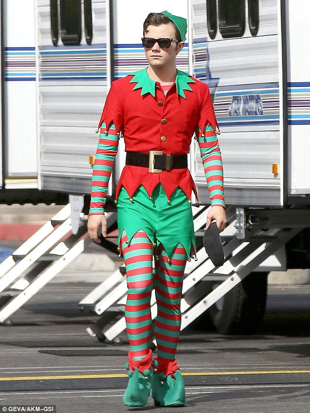 Ready to roll: Chris was picture-perfect in his green shorts and red shirt, worn over a red and green striped long-sleeved top and leggings, while he jazzed up his ensemble with black Ray-Bans as he strolled around set between scenes