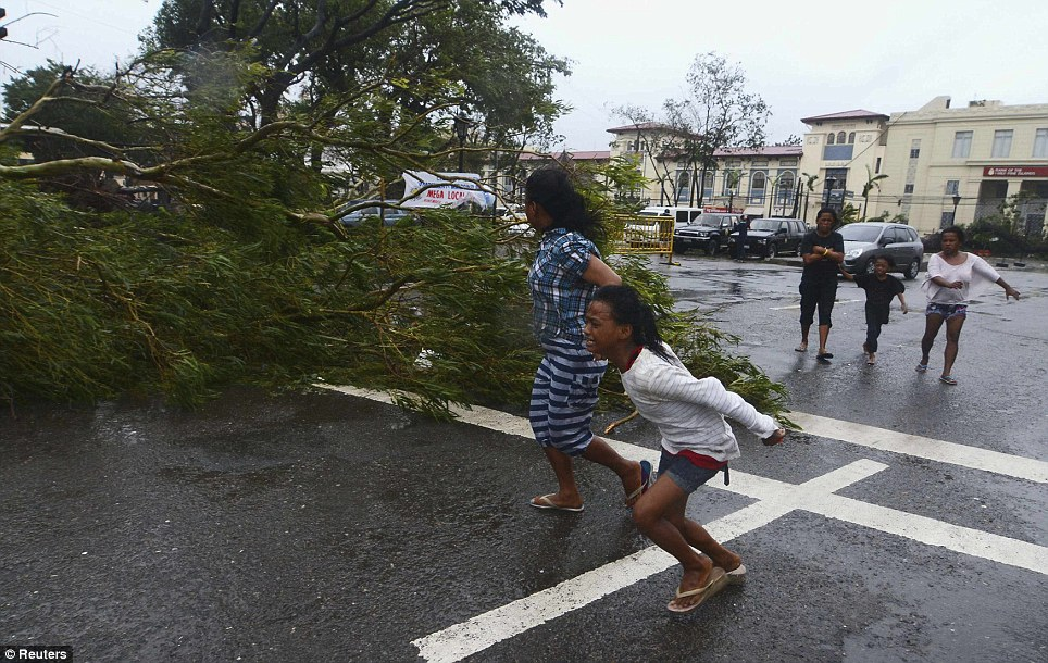 Terrifying: Residents run for their lives as the terrible gusts of the typhoon rush buffet the popular tourist city of Cebu