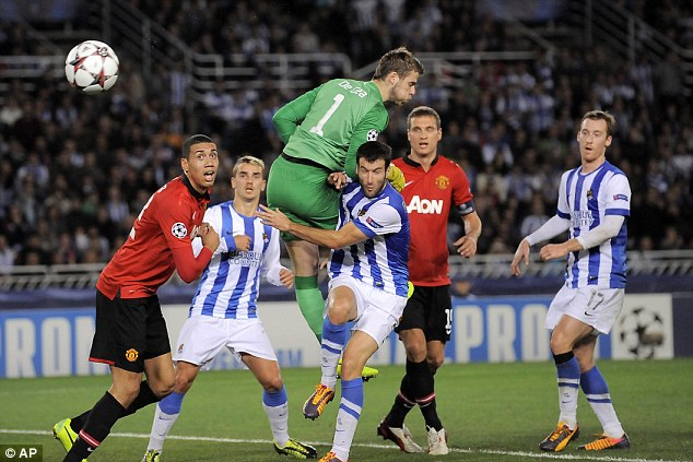 In action: De Gea tries to keep Real Sociedad's attackers at bay in the Champions League clash
