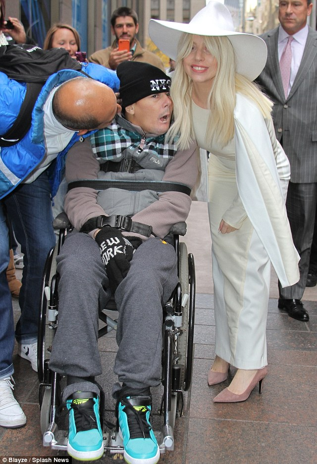 Loves her little monsters: Gaga stopped to pose with a disabled fan outside of Z-100 studios