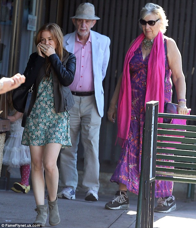 She's got the giggles: The Australian actress covered her mouth to suppress her laughter, as Sacha's parents walked close behind her