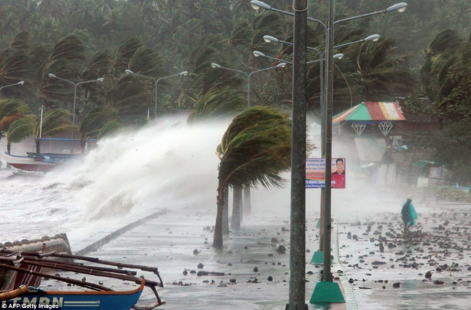 Higher ground: Residents of  Legaspi, Albay province, south of Manila resident, were forced to flee the coast as Haiyan continued to pound the sea wall today