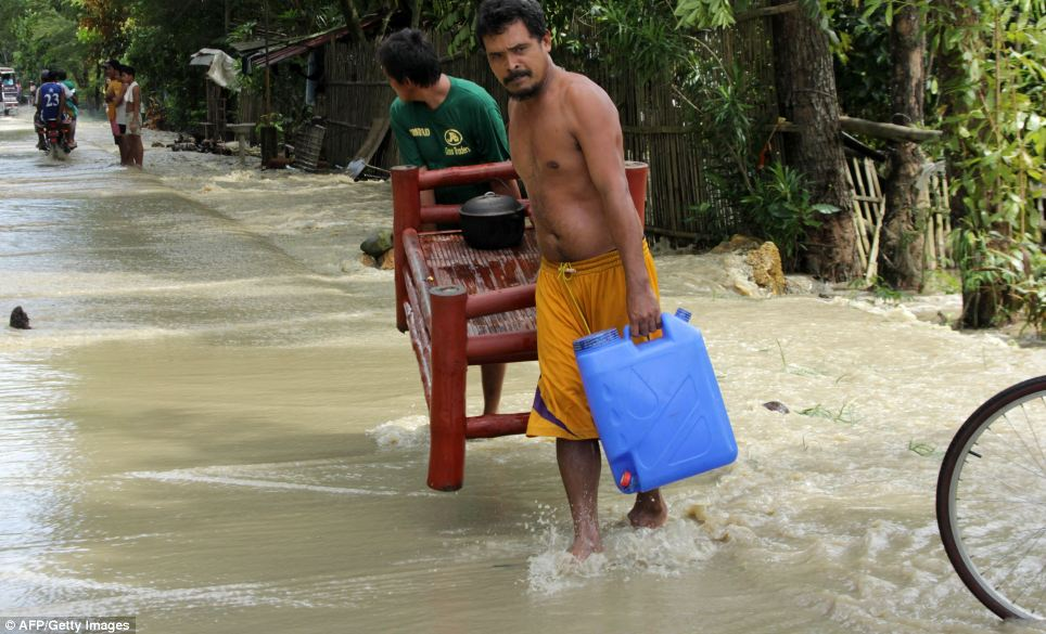 Rebuilding their lives: Two men in Iloilo move some of their belongings through flood waters covering the streets