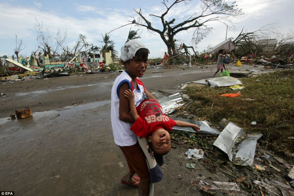 Terrifying: Filipino children are seen in the city of Tacloban, Leyte. Behind them is a scene of devastation with homes flattened and debris lying in the street