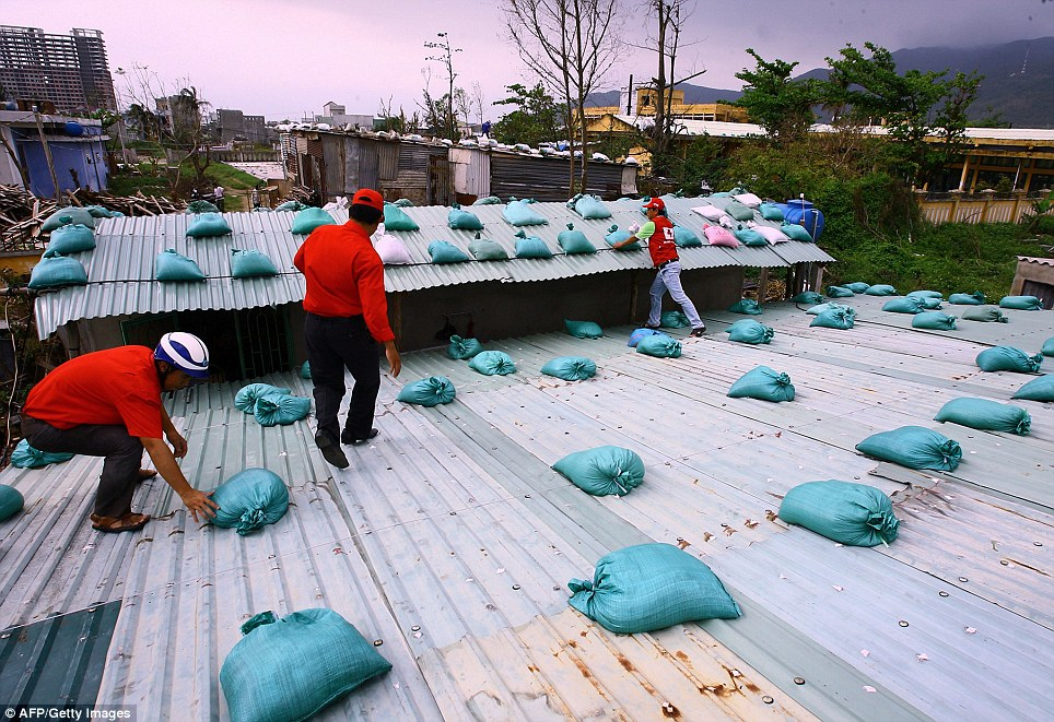 Workers: Local Red Cross staff place sand bags on the roof of a house in  Danang, Vietnam