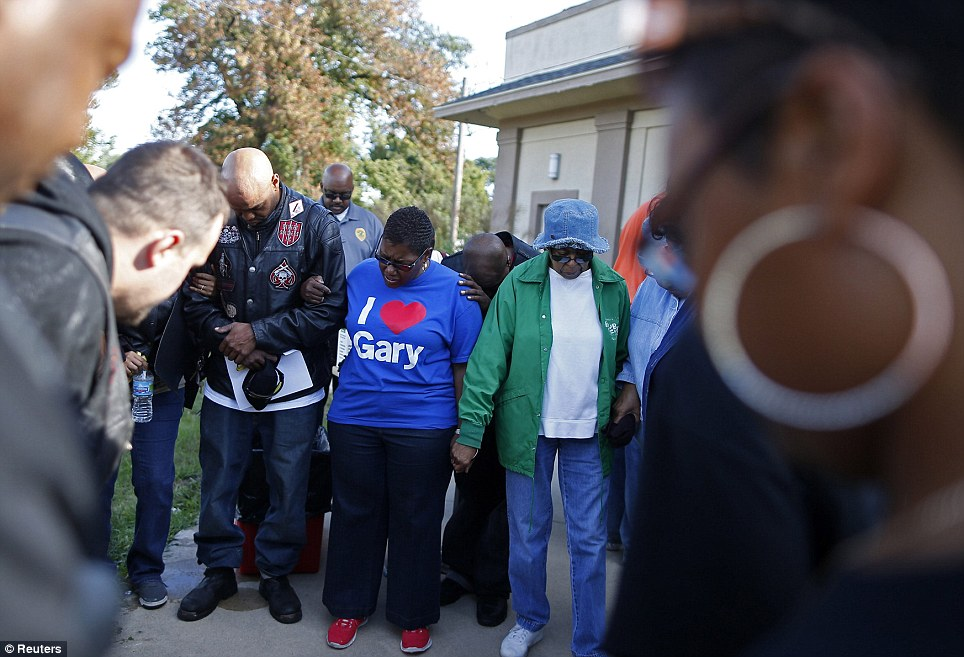 Higher power: Mayor Karen Freeman-Wilson (center) takes part in a group prayer before the start of a neighborhood clean-up
