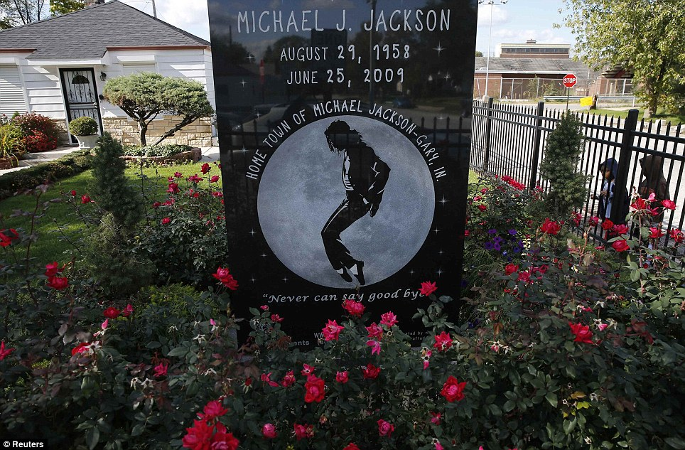 Claim to fame: Two boys look through the fence surrounding the childhood home of singer Michael Jackson, who was born and spent part of his youth in Gary