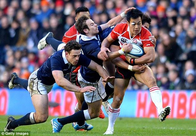 Strength: Japan's Kenki Fukuoka is tackled by  Ruaridh Jackson and Nick De Luca