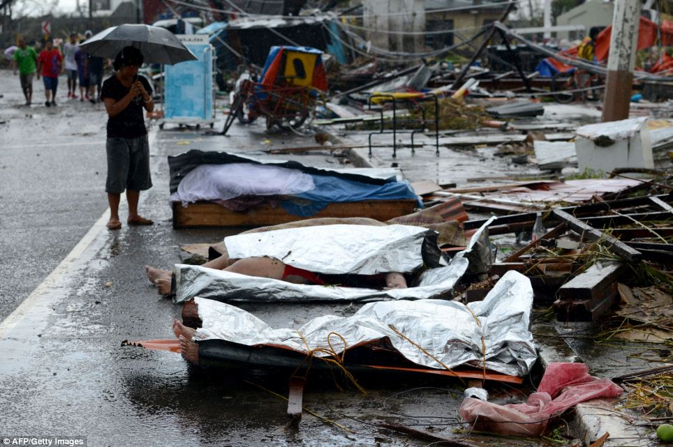 A woman mourns in front of her husband's dead body, which lies no the street under tarpaulin alongside other bodies
