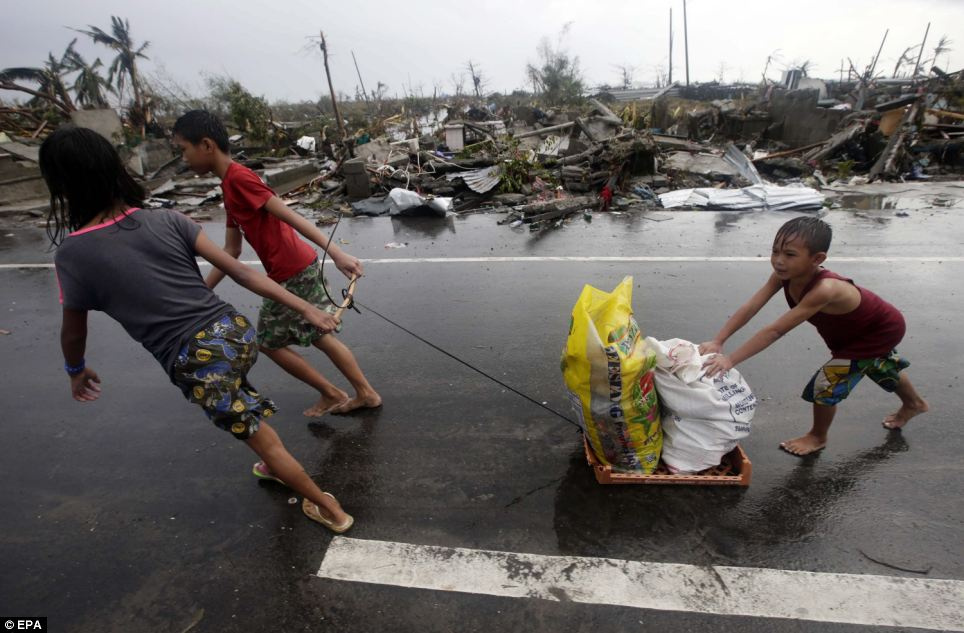 Children pull sacks of goods they recovered from abandoned stores as they go past the rubble of houses in  Tacloban