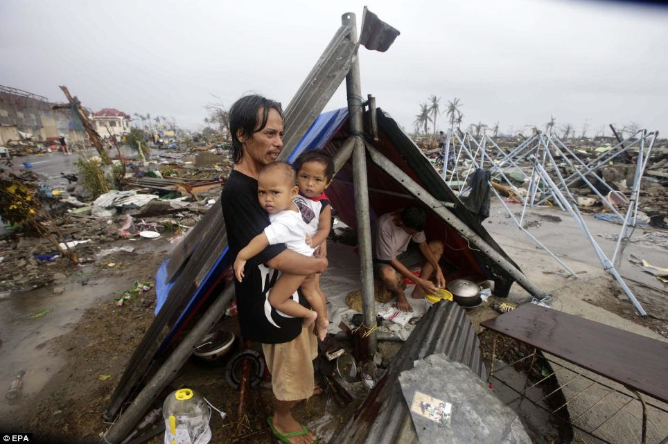 A Filipino father and his children wait for food relief outside their makeshift tent.