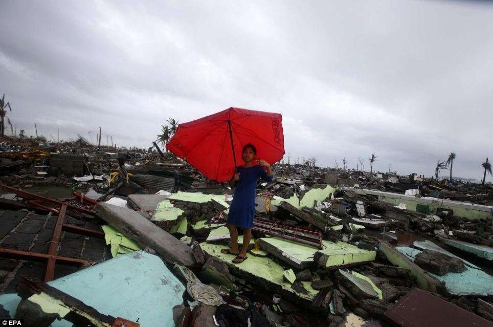 A woman holds her umbrella stands on debris of houses in Tacloban