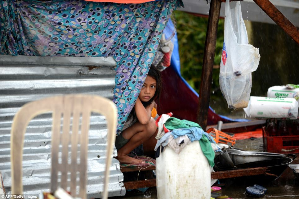 A girl looks out from a makeshift shelter in Tacloban.