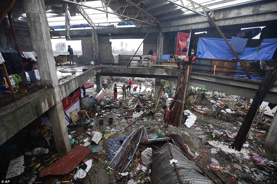 Aftermath: Resident gather in the remains of a structure in Tacloban. Those left homeless have been forced to plunder the houses belonging to the dead. One local councillor admitted he has stepped on corpses in a desperate bid to find food