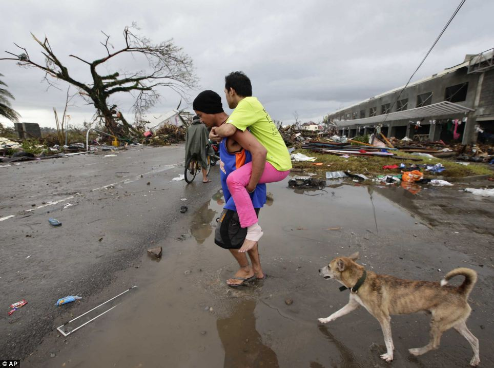 A man with an injured leg is carried through the devastation of former residential roads in Tacloban