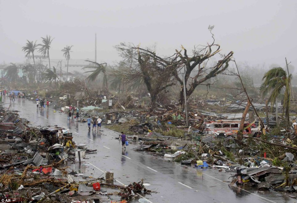 City of the dead: Dazed survivors survey the damaged houses in Tacloban city, Leyte province. At least 10,000 people are believed to have died there