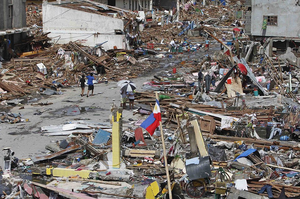 Remains: Survivors have begun to rummage through the wreckages of houses in a bid to find food to feed their families
