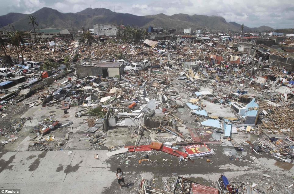 Bodies still lie in the roads and thousands of homes lie destroyed near the fish port after super Typhoon Haiyan battered Tacloban city