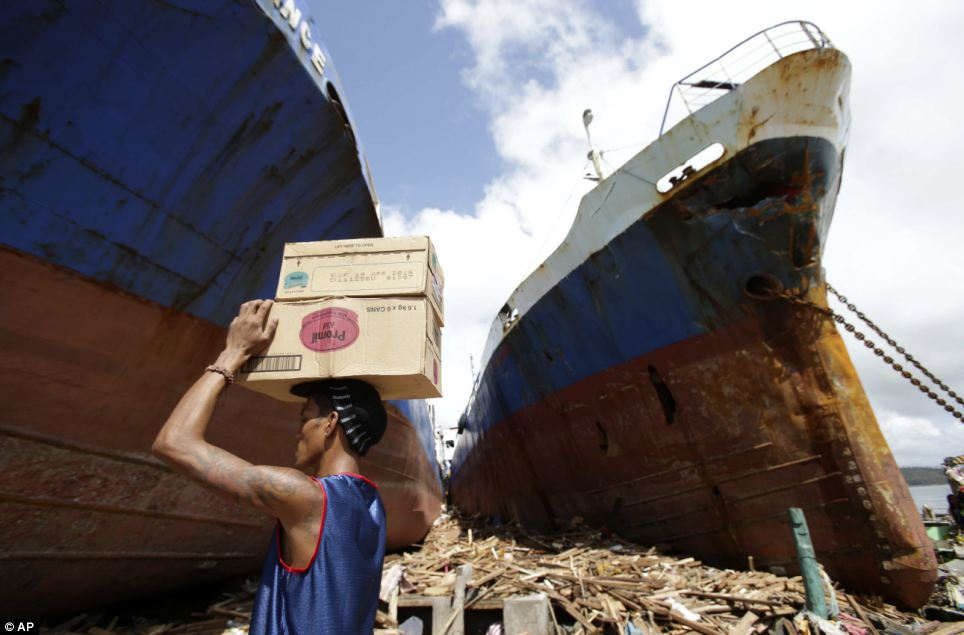 A man carries boxes of milk as he passes by ships washed ashore by enormous waves in Tacloban city, Leyte province