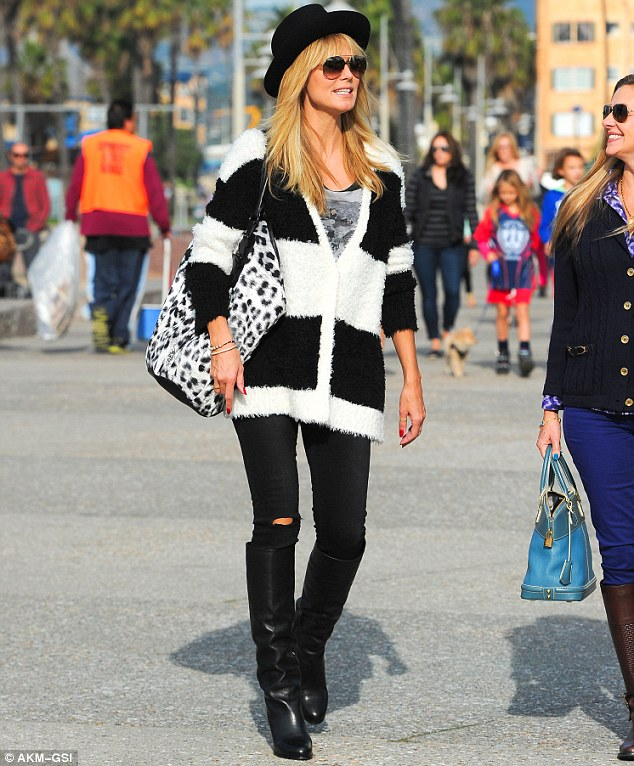 Soccer mum: The 40-year-old wore a fashionable ensemble that featured a wide brimmed hat and tight black jeans