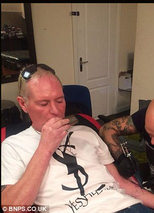 Artist Robbie tattoos Gazza's arm while Gazza plays the harmonica.