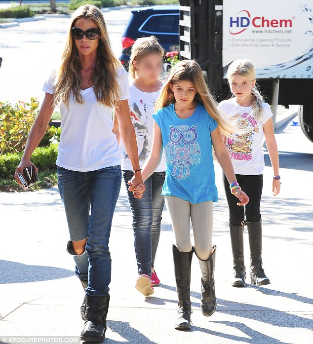 Hand-in-hand: Denise was casually dressed in ripped jeans and a white T-shirt as she walked along hand-in-hand with Sam while Lola held hands with a pal