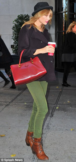 Nice accessory: The beauty carried a fashionable red purse that brightened up her autumn ensemble