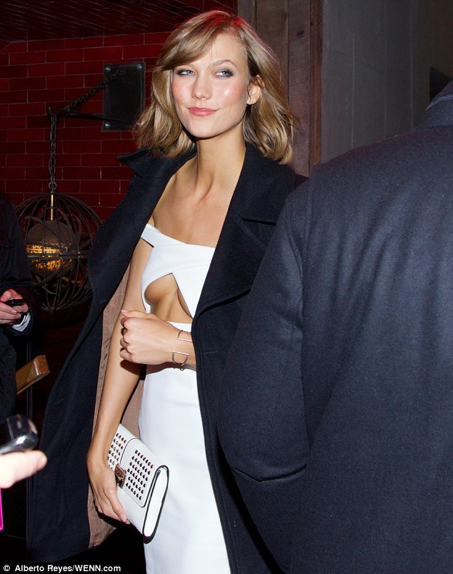 Cover up: Karlie arrived at the party in a winter coat and showed off a great deal of cleavage in her white dress
