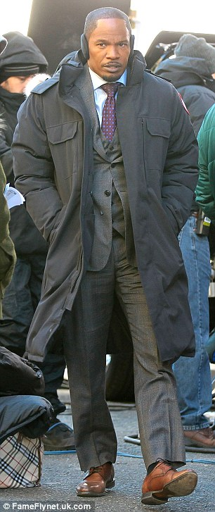 Mighty fine: The actor strut about set looking dashing in a suit and a suave trench to keep warm