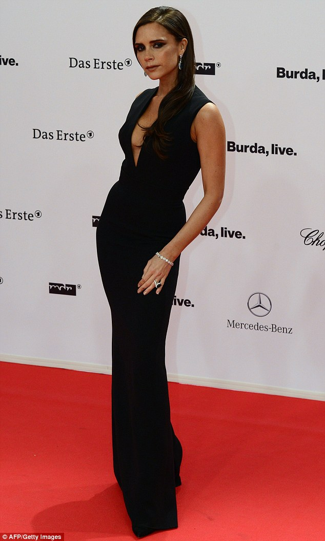 Super sleek: The fitted dress hugged Victoria's svelte figure as she posed up a storm on the red carpet