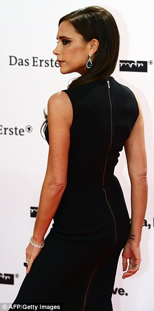 Working it: Victoria posed solo on the red carpet ahead of her acceptance of the fashion award
