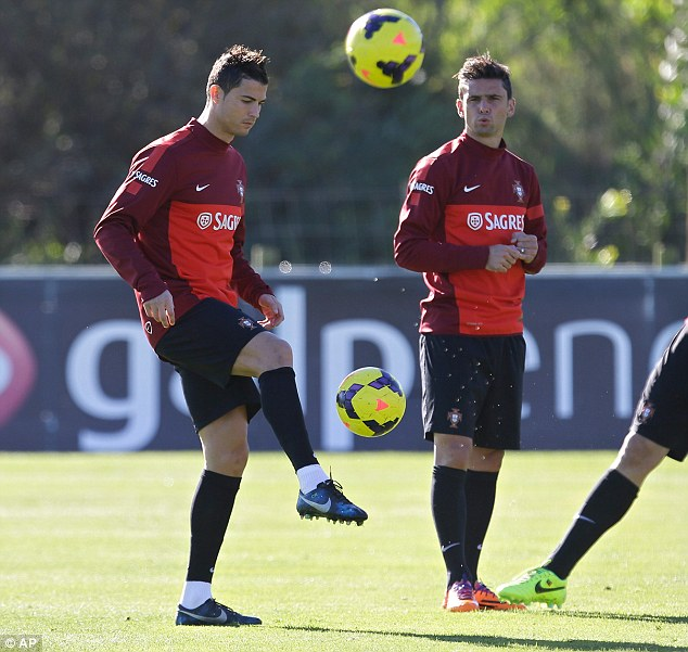 Control: Cristiano Ronaldo (left) does keep-ups in Portugal training with with Helder Postiga watching on