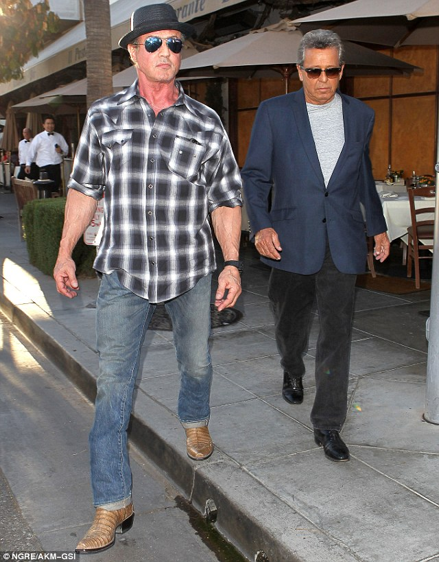 Cool boots: Sly looked slick in his plaid shirt, blue jeans and tan boots as he left lunch with an unidentified friend