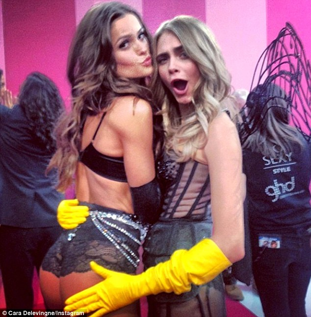 Cop a feel! Cara Delevingne posted a saucy picture from behind the scenes of the Victoria Secret fashion show patting Izabel Goulart's pert derriere