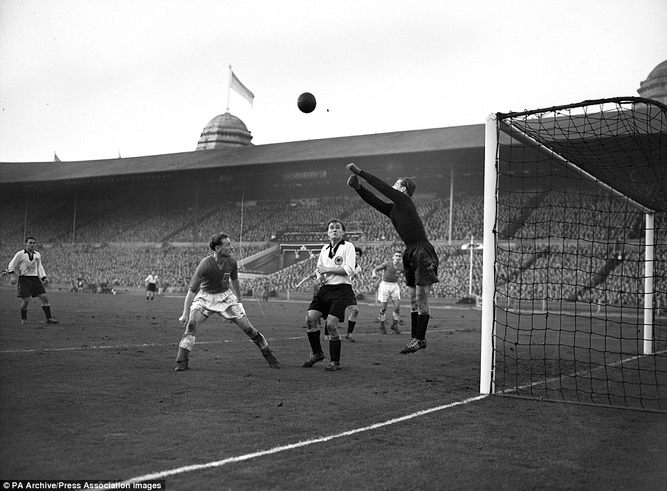 Fritz Herkenrath, Germany's goalkeeper punches clear a shot from England's Roy Bentley as Tom Finney (left) waits for a chance. England won 3-1.