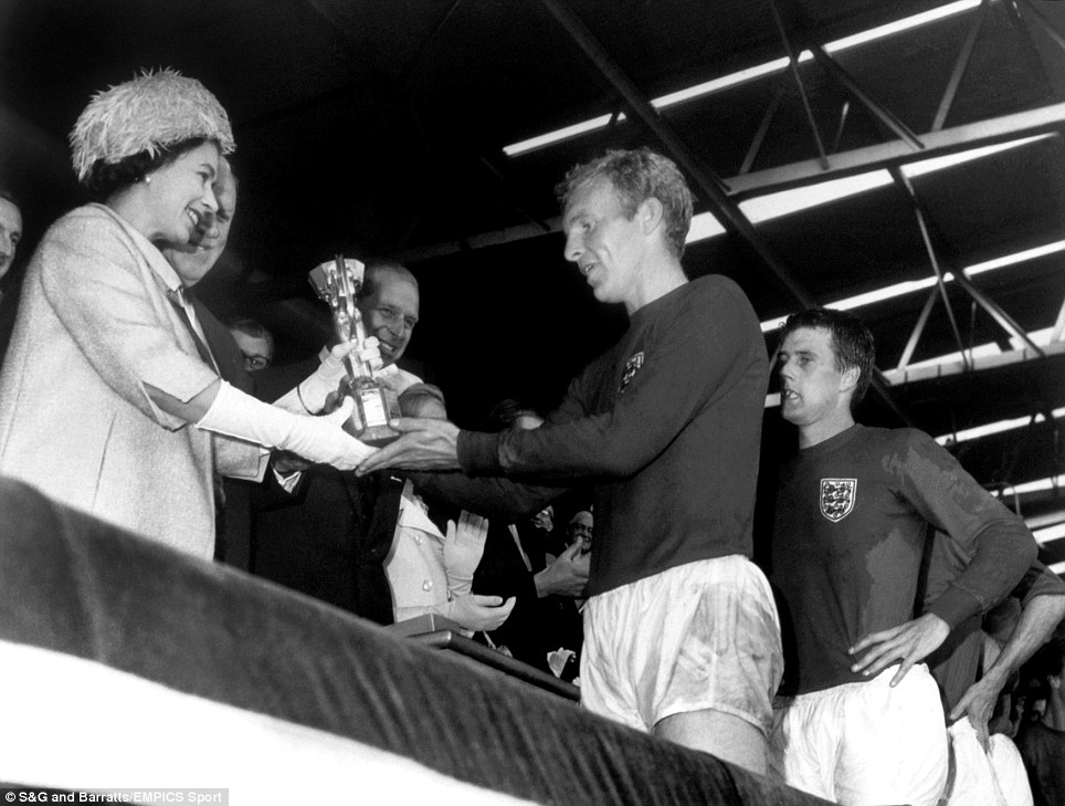England captain Bobby Moore is presented with the Jules Rimet trophy by Her Majesty The Queen as teammate Geoff Hurst (r) looks on in awe