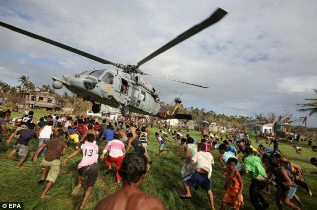 Desperation: Filipino typhoon victims rush to get relief goods from a U.S. Navy Sea Hawk in Salcedo