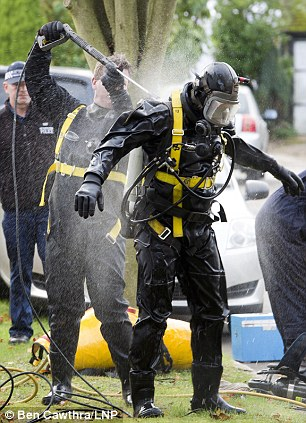 Cleaned: A police specialist diver being washed down after leaving the scene