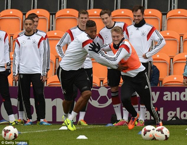 Tussle: Jerome Boateng (left) and Andre Schurrle of Germany go shoulder to shoulder during training