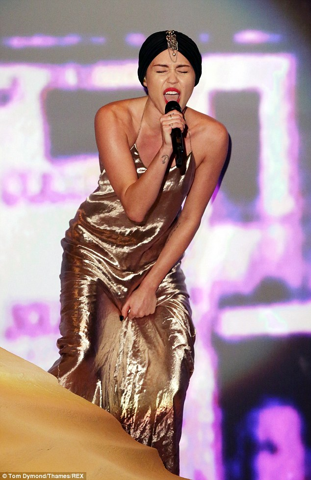 A whole new world: Miley emerges from the fake sand dune on the X Factor stage