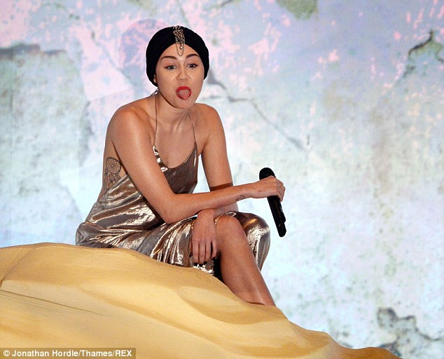 There it is again! Miley Cyrus couldn't resist sticking her tongue out mid-song while sitting on her fake sand dune on The X Factor
