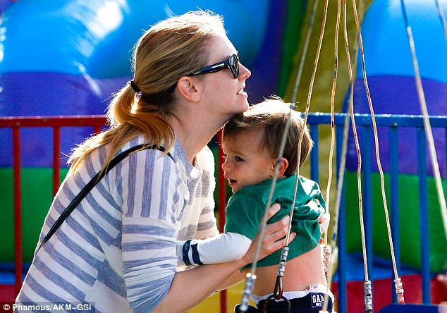 Take a spin: Hart readies her one-year-old son for a thrill ride