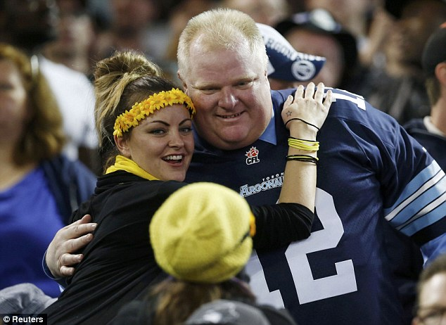 Ford poses with a fellow Canadian Football League fan after making an appearance at the Rogers Centre - despite being warned off by the CFL commissioner