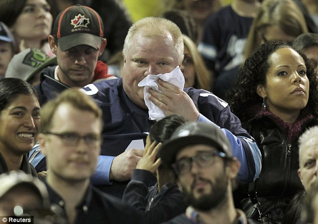 Working up a sweat: Toronto Mayor Rob Ford mops his brow as he watches the CFL eastern final football game between the Toronto Argonauts and the Hamilton Tiger Cats