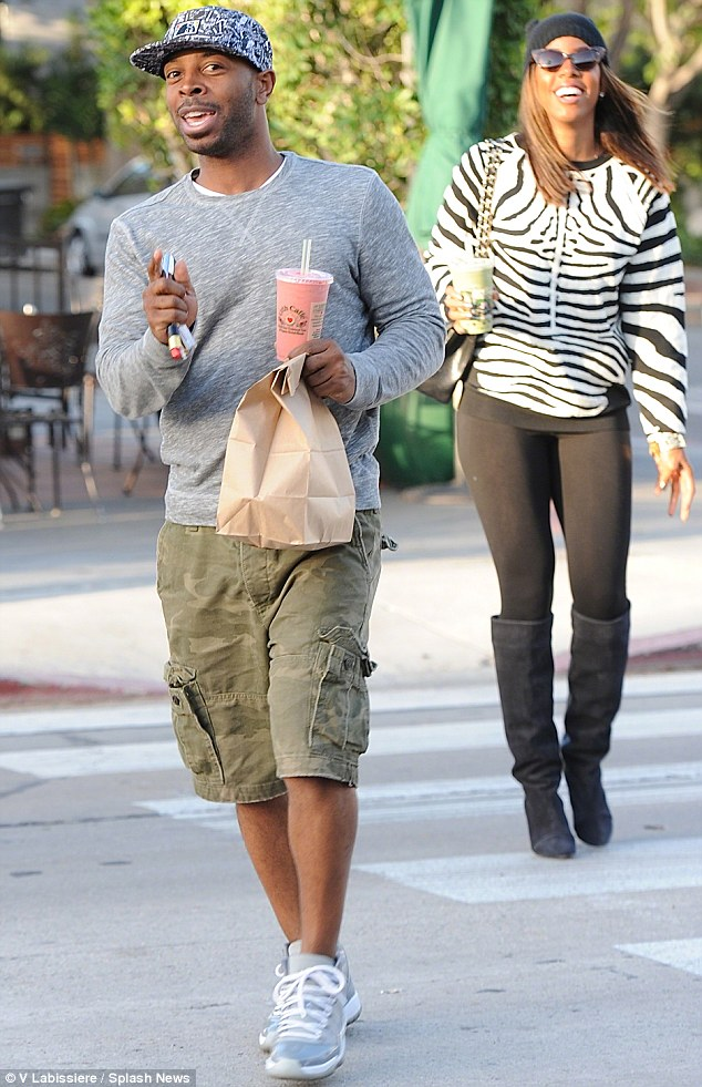 Low profile: Kelly pictured with Tim in October leaving a cafe in Los Angeles; their pair have been dating on-off for four years but keep their relationship low profile, seen here walking apart when spotted by the paparazzi